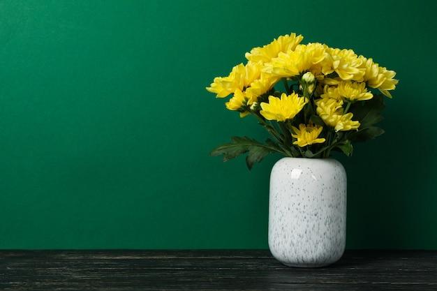 Vaas met gele chrysanten op houten tafel, ruimte voor tekst