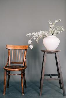 Vaas met groene plant op houten vintage stoel