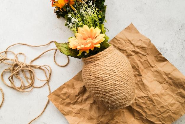 Vaas met koord op verfrommeld pakpapier tegen witte achtergrond wordt gemaakt die