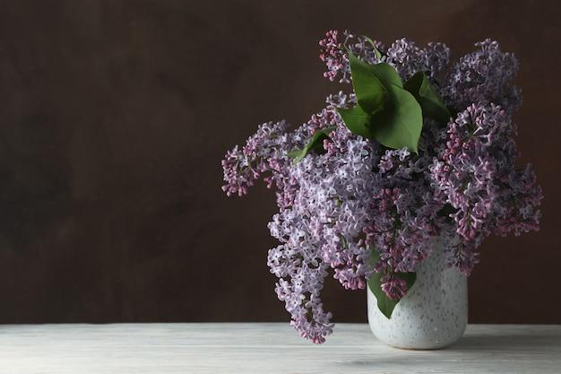 Vaas met lila bloemen op bruine achtergrond, ruimte voor tekst
