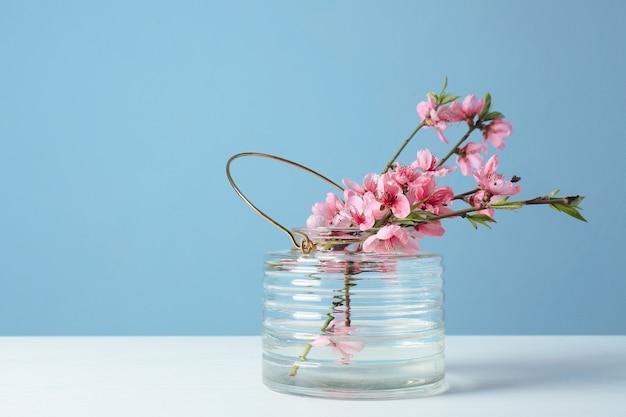 Vaas met mooie bloeiende takken op tafel tegen gekleurde achtergrond