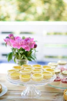 Vaas met pioenrozen bloemen en desserts op een houten picknicktafel in de zomer. vakantie met het gezin.