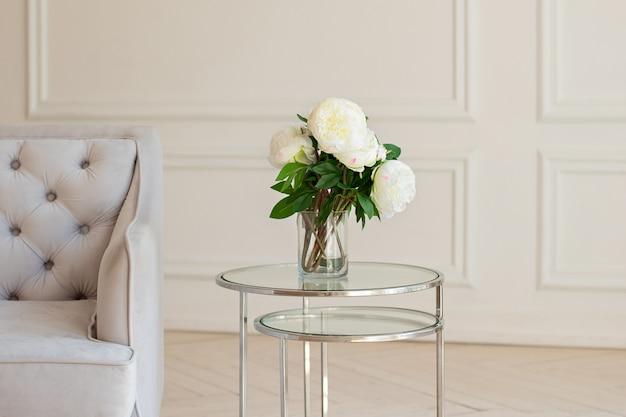 Vaas met prachtige pioenroos bloemen op tafel in de buurt van een grijze bank in de woonkamer. gezellige huisdecoratie, verse witte pioenrozen op salontafel in witte kamer.