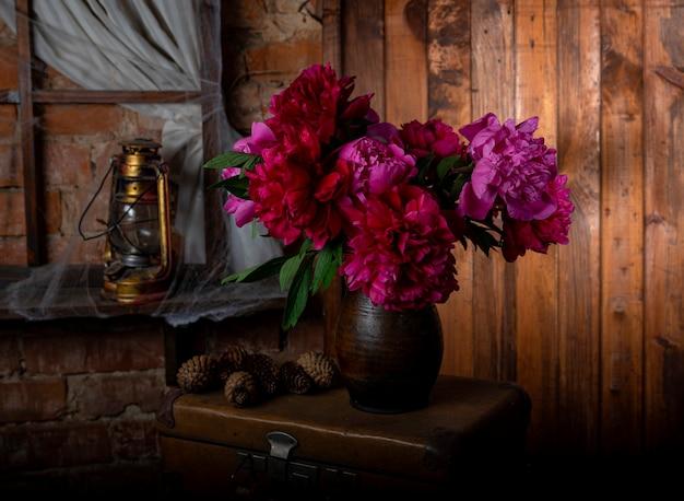 Vaas met prachtige rood bloeiende pioenrozen