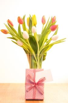 Vaas met tulpen op houten tafel met cadeau en lege kaart