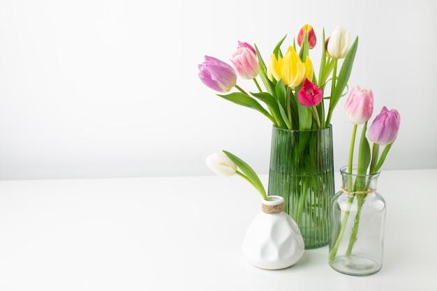 Vaas met tulpen op tafel Gratis Foto