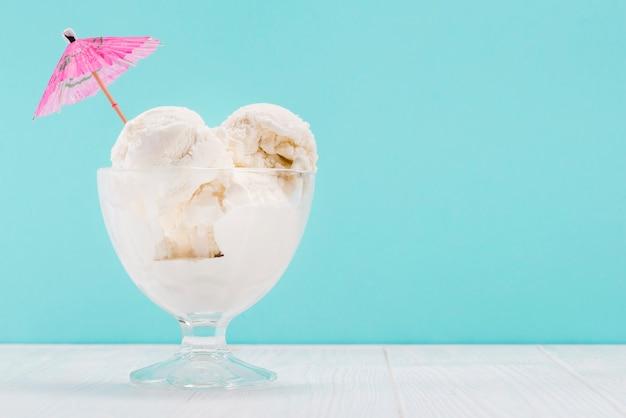 Vaas met vanille-ijs met roze paraplu erop