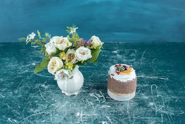 Vaas met witte bloemen en een kleine cake op blauw.