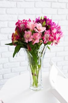Vaas vol kleurrijke bloemen op tafel