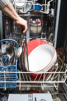Vaatwasser met vuile vaat close-up. huishoudelijke keukenapparatuur. assistent gastvrouw.