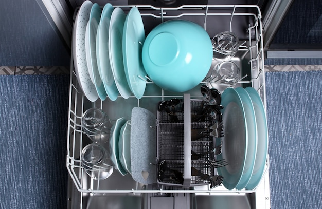 Vaatwasser openen met schoon keukengerei erin. bovenaanzicht. schone borden, glazen, vorken, lepels na het wassen in de vaatwasser. vaatwasser na het reinigingsproces.