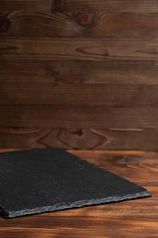 Vaatwerk leisteen, zwarte steen op een houten achtergrond.