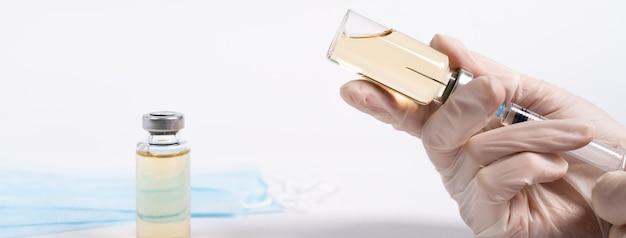 Vaccin en medische maskers, de handen van de dokter typen het vaccin in de spuit, covid 19