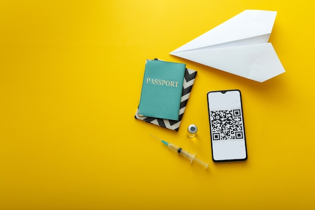 Vaccin en spuit covid 19 groen paspoort qr-code op smartphonescherm en papieren vliegtuig. digitaal certificaat corona-vaccinpas gratis reizend internationaal elektronisch vaccinatiepaspoort. geel.