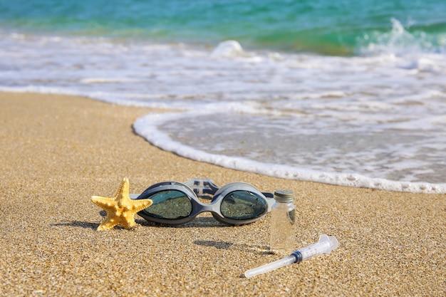 Vaccin tegen covid-19, spuit, duikbril en zeester op strand.