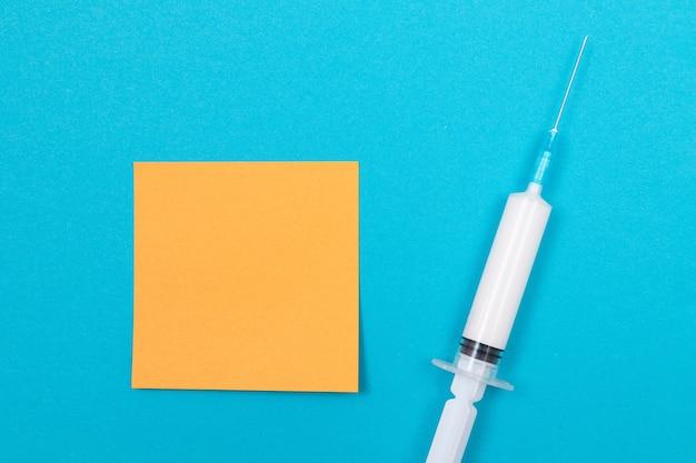 Vaccinatie of hervaccinatie concept een medische spuit op blauwe tafel