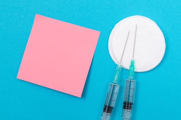 Vaccinatie of hervaccinatie concept twee medische spuit op blauwe tafel