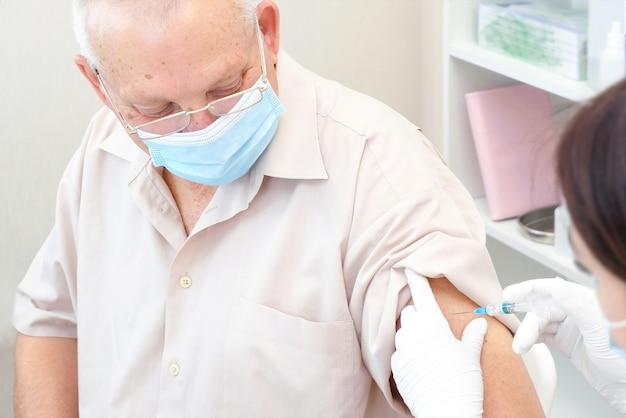 Vaccinatie van een volwassen persoon in een ziekenhuis. gezondheidszorgconcept, coronavirusvaccin