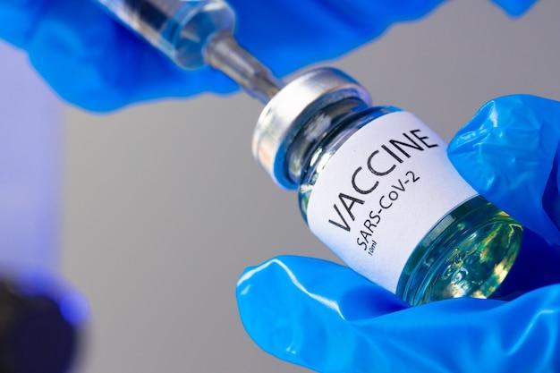 Vaccinfles met een spuit die het vaccin eruit haalt