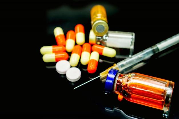 Vaccins in injectieflacon, capsules en witte pil-medicijnen met een plastic spuit op zwart.