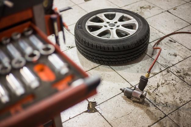 Vacuümpistool voor het vervangen van wielen van de auto op de vloer, transportconcept