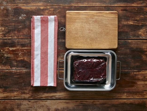 Vacuümverpakking van walvisvlees steak metalen pot met handdoek en houten plaat, bovenaanzicht
