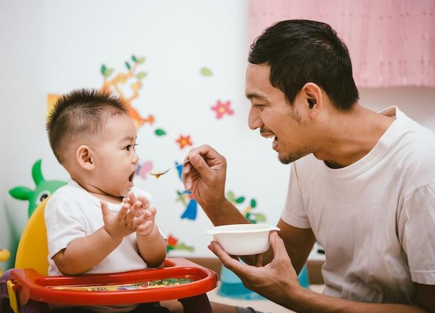 Vader acteren moeder voeden zijn zoon baby 1 jaar oud op stoel in het huis