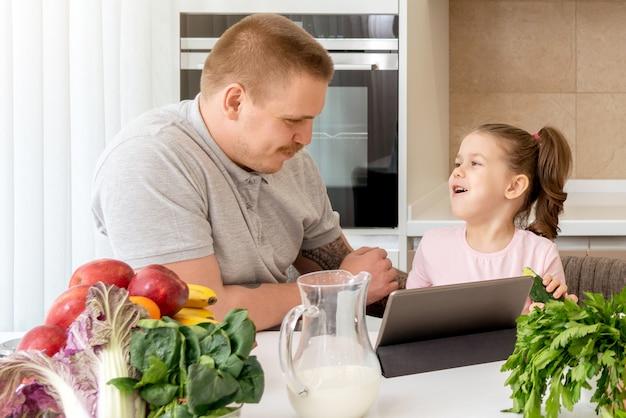Vader and daughter die digitale tablet in keuken thuis gebruiken