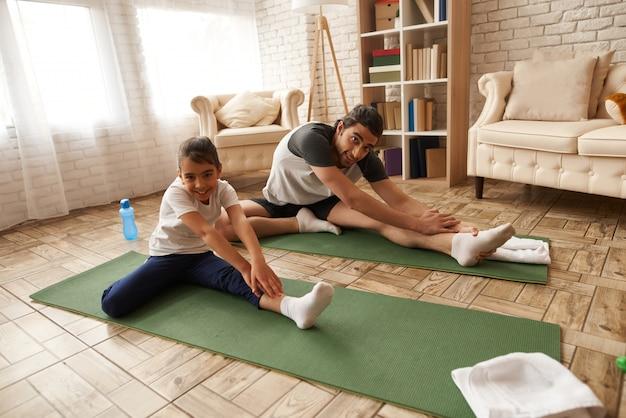 Vader and daughter stretch legs op gymnastiektapijt.