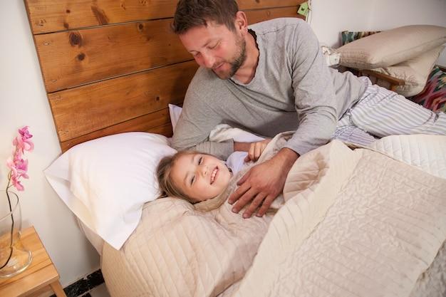 Vader bedekt zijn dochter met het dekbed