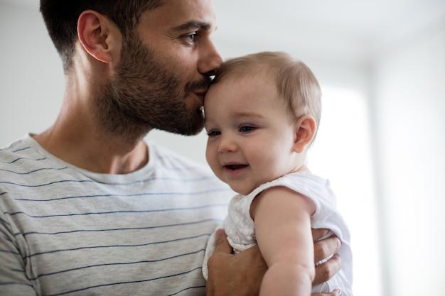 Vader bedrijf zoenen zijn babymeisje op voorhoofd thuis