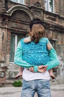 Vader blijf achter en draag meisje in draagdoek