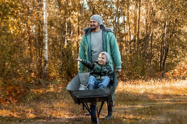 Vader brengt tijd door met zijn zoon, een gelukkige kleine jongen die door een vader wordt geduwd
