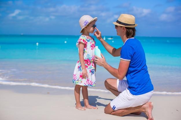 Vader brengt zonnebrandcrème aan op de neus van zijn dochtertje