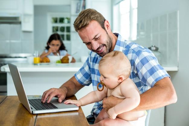 Vader die babyjongen bekijkt terwijl thuis het gebruiken van laptop