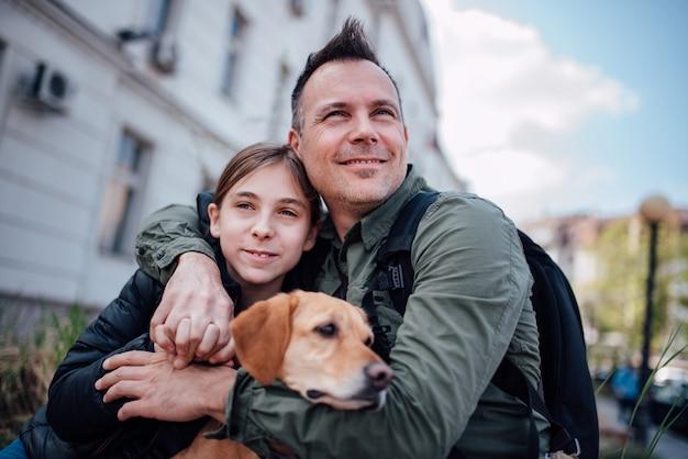 Vader die dochter en hun kleine hond in openlucht omhelst
