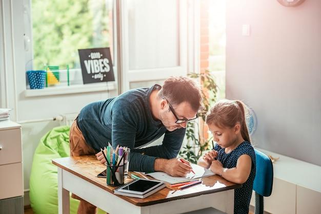 Vader die dochter helpt om huiswerk te beëindigen