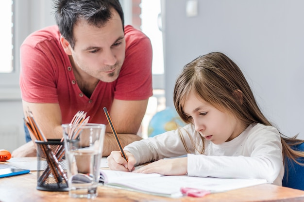 Vader die dochter met huiswerk helpt