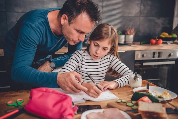 Vader die dochter met huiswerk in keuken helpt