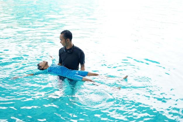 Vader die dochter onderwijst om te zwemmen