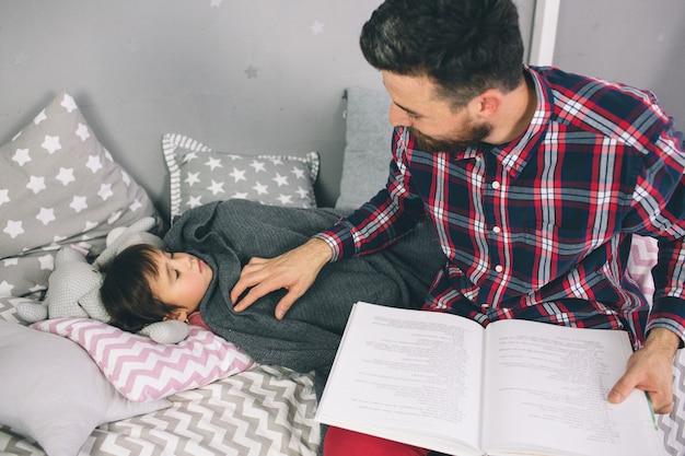 Vader die een boek leest aan zijn dochter terwijl het liggen op het bed in slaapkamer
