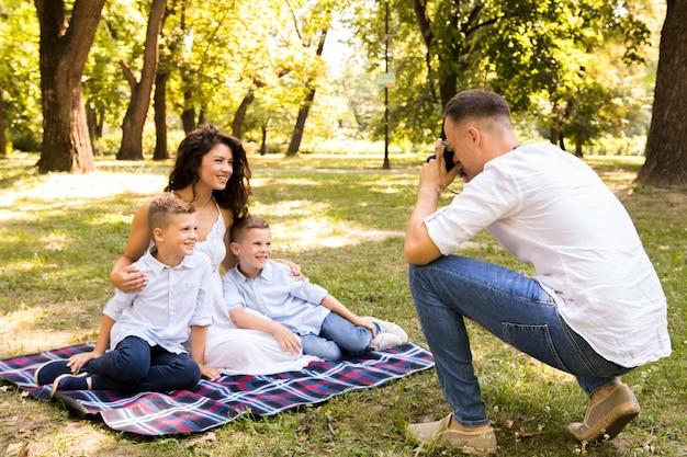 Vader die een foto van zijn familie neemt