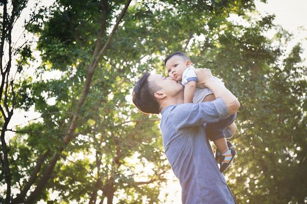 Vader die in hand zoon opheft en beweert te rijden met plezier, lifestyle en familieconcepten