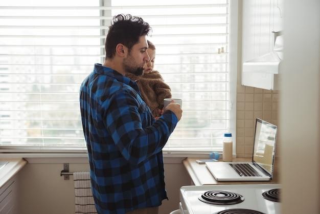 Vader die koffie drinkt terwijl hij zijn baby vasthoudt