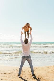 Vader die lachend kind omhoog in hemel werpt