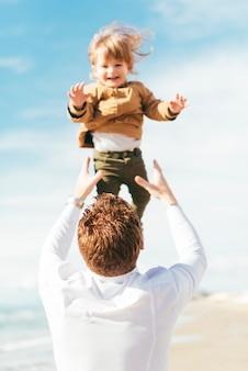 Vader die lachende zoon omhoog in hemel werpt