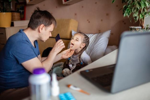 Vader die laptop het scherm bekijken en thuis online een arts raadplegen
