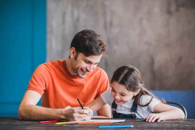 Vader die met dochter op vadersdag schilderen