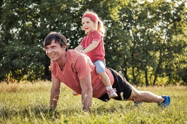 Vader die met zijn jonge dochter in openlucht speelt