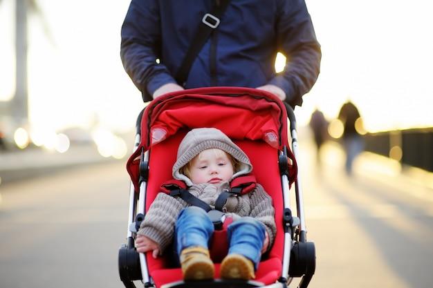 Vader die met zijn peuterzoon loopt in wandelwagen